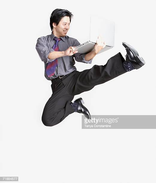 Studio shot of Asian businessman jumping in air with laptop