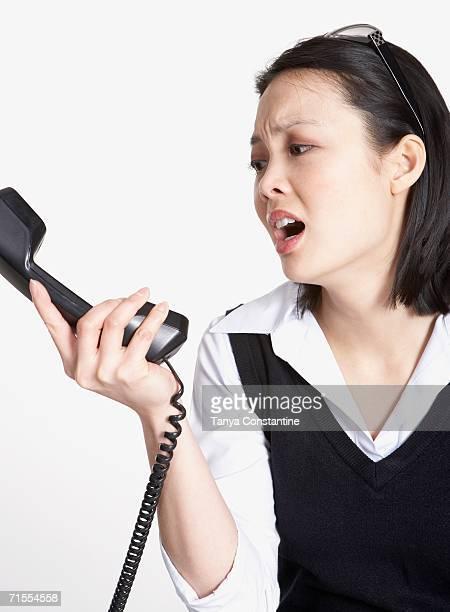 Studio shot of Asian businesswoman yelling at telephone