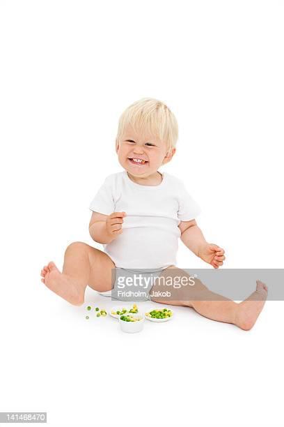 Studio shot of baby boy eating peas