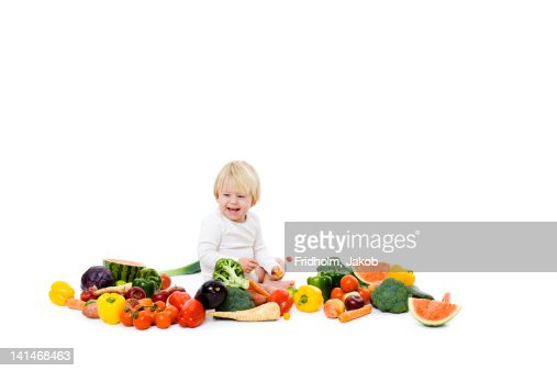 Studio shot of baby boy surrounded by fresh vegetables : Stock Photo