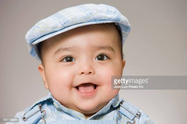 Studio shot of baby boy wearing hat and smiling