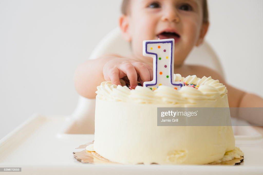 Studio shot of baby (12-17 months) reaching for cake