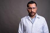 Studio shot of bearded Persian man doctor against gray background horizontal shot