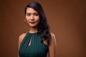 Studio shot of beautiful Asian businesswoman wearing formal green dress against colored background horizontal shot
