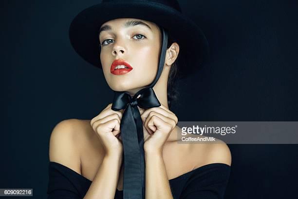 Studio shot of beautiful woman wearing black hat