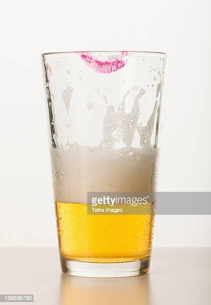 Studio shot of beer glass with lipstick mark on edge