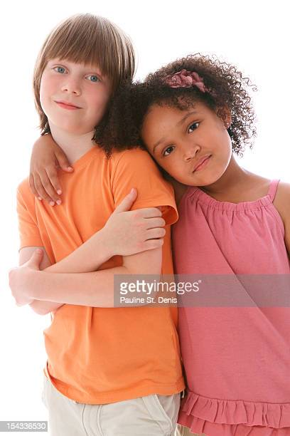 Studio shot of boy (8-9) and girl (6-7) standing and leaning on each other