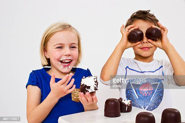 Studio shot of brother and sister with chocolate marshmallows