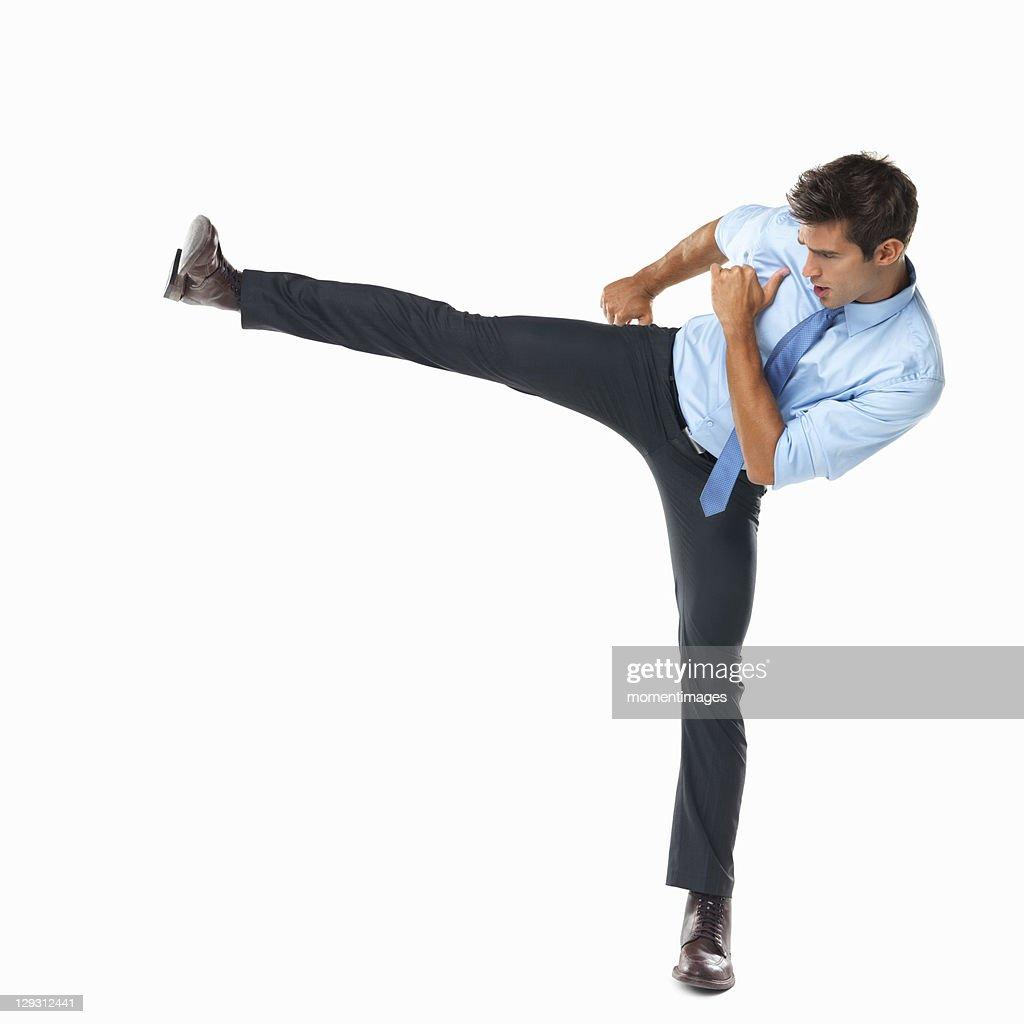 Studio shot of business man delivering high side kick