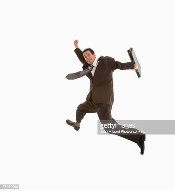 Studio shot of businessman jumping with briefcase