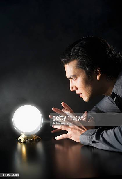Studio shot of businessman looking at crystal ball