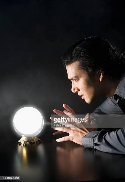 Studio shot of businessman looking at crystal ball