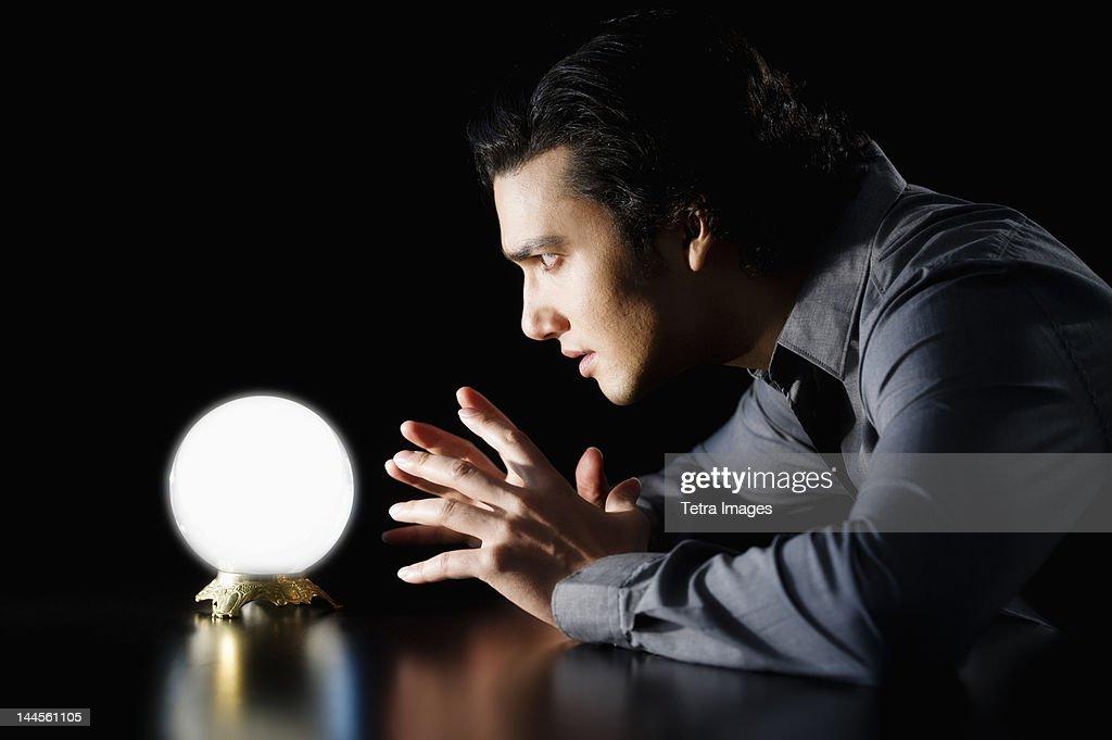 Studio shot of businessman staring at crystal ball : Stock Photo