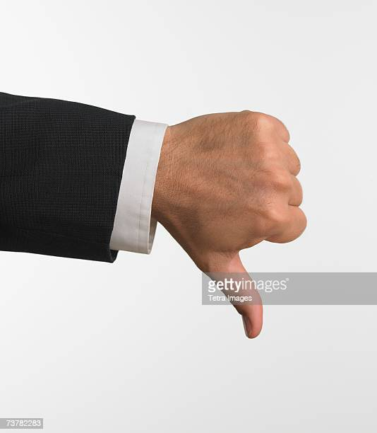 Studio shot of businessman's hand giving thumbs down