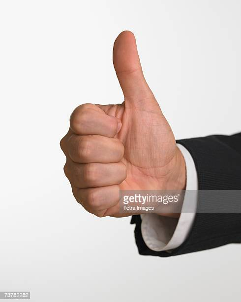 Studio shot of businessman's hand giving thumbs up