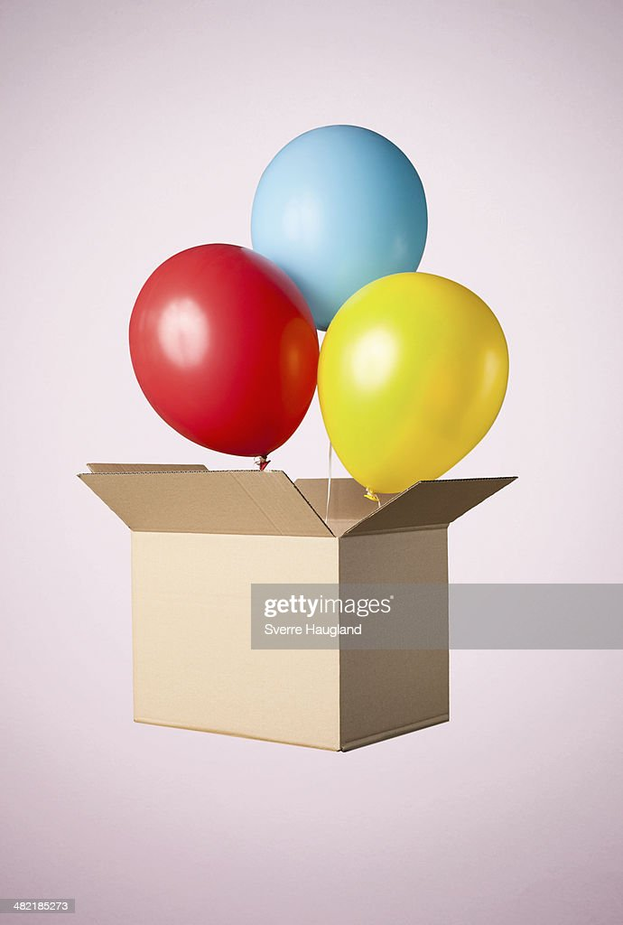 Studio shot of cardboard box with balloons coming out : Stock Photo