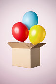 Studio shot of cardboard box with balloons coming out