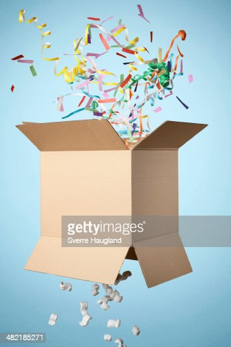 Studio shot of cardboard box with streamers exploding out