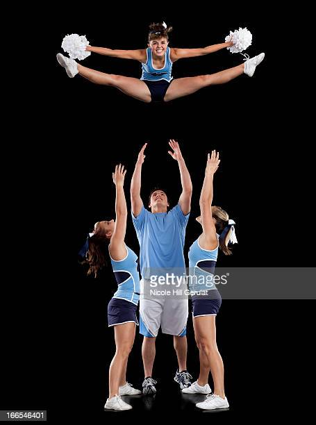 Studio shot of cheerleaders (16-17) assisting friend during jump