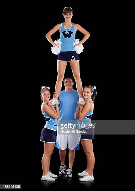 Studio shot of cheerleaders (16-17) assisting friend during performance