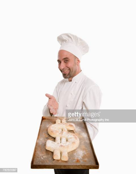 Studio shot of chef with bread in the shape of a dollar sign