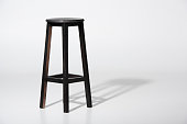 Studio shot of classic black tall wooden barstool standing on white