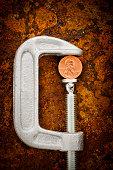 Studio shot of coin in vise grip