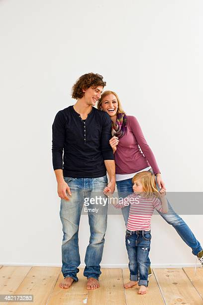 Studio shot of couple holding hands with young daughter