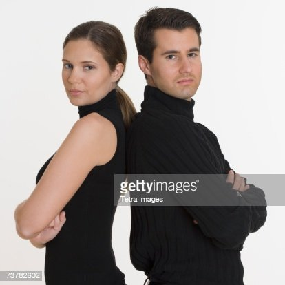 Studio shot of couple standing back to back
