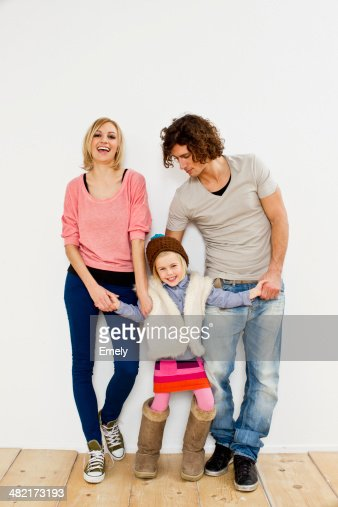 Studio shot of couple with young daughter wearing big boots