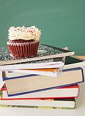 Studio shot of cupcake on stack of books