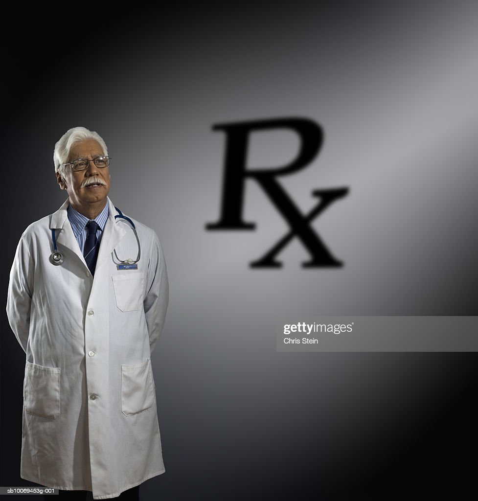 Studio shot of doctor and RX sign behind : Stock Photo