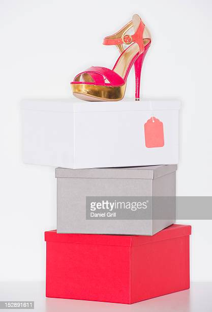 Studio shot of dress shoe on top of stack of boxes