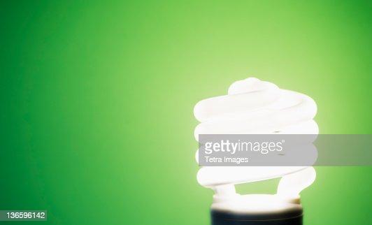 Studio shot of energy efficient lightbulb on green background : Stock Photo