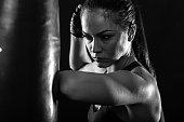 Studio shot of female boxer punching a boxing bag.