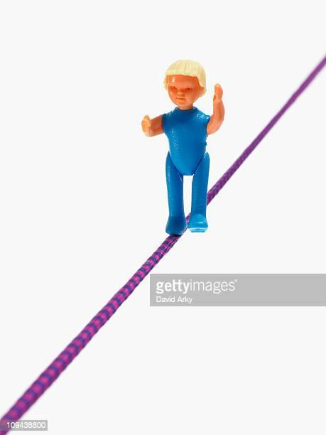 Studio shot of figurine balancing on tightrope