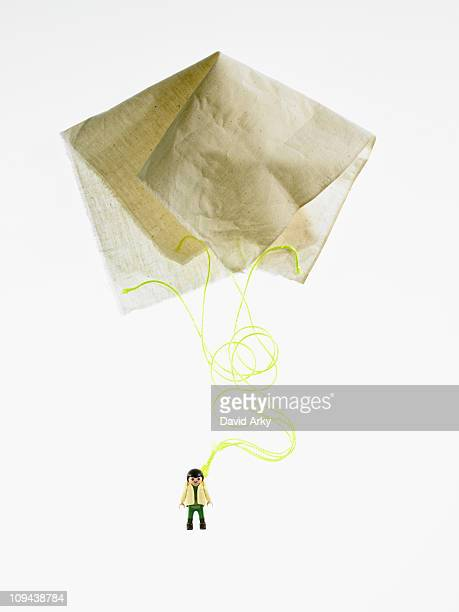 Studio shot of figurine with paper parachute