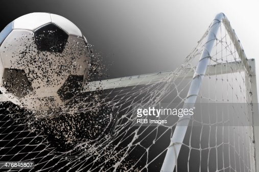 Studio shot of football powering through goal netting : Stock Photo