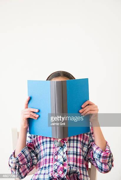 Studio shot of girl (12-13) hiding behind open book