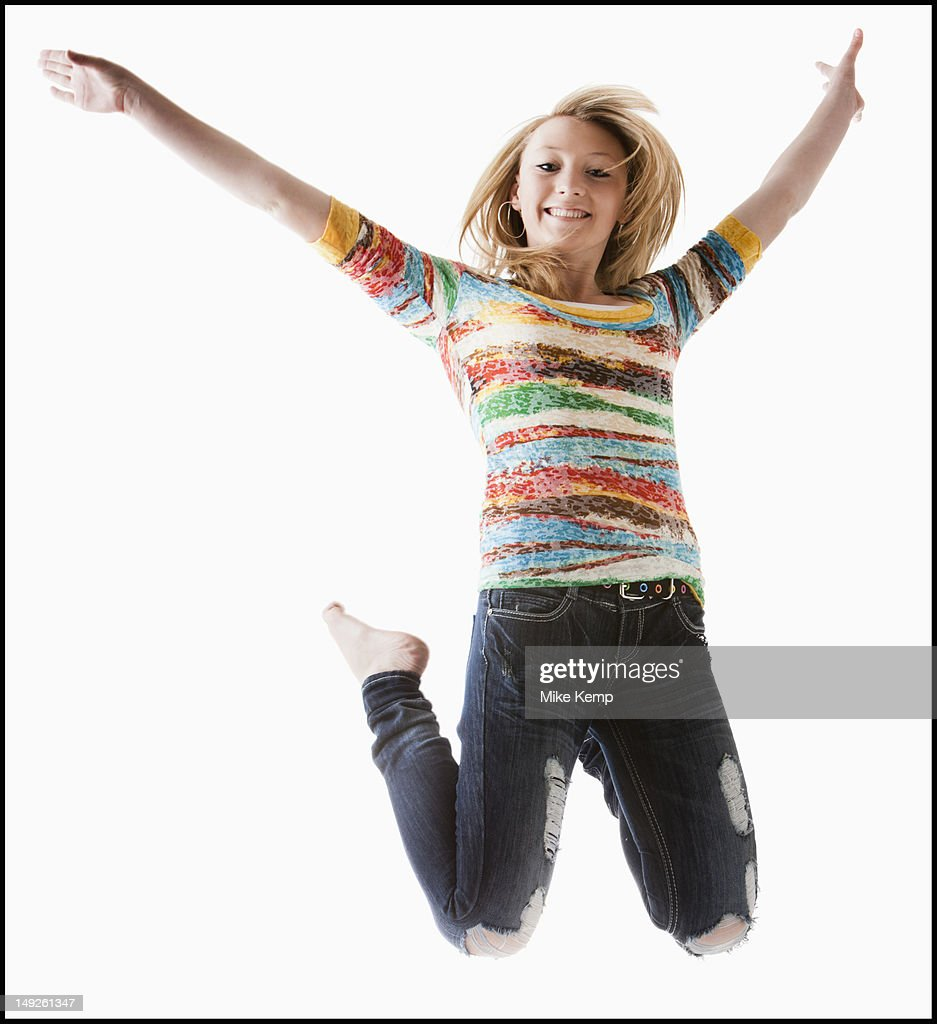 Studio shot of girl (12-13) jumping with arms raised : Stock Photo