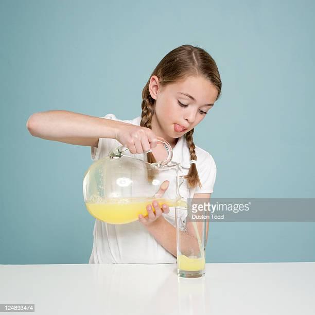 Studio shot of girl (10-11) pouring lemonade