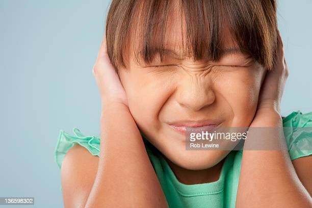 Studio shot of girl (10-11) with closed eyes covering ears