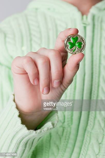 Studio shot of girl's (10-11) hand holding clover-shaped button