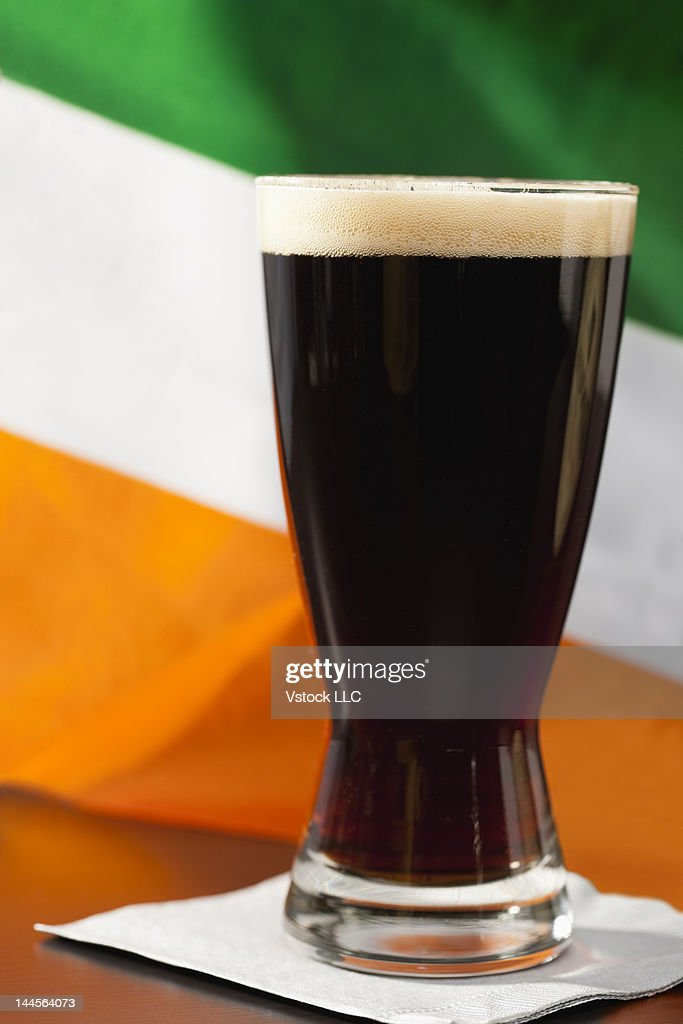Studio shot of glass of stout beer with Irish flag