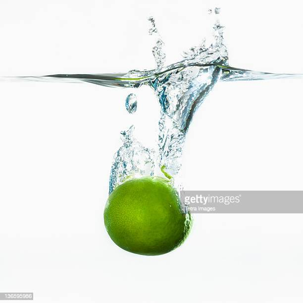 Studio shot of green apple falling into water