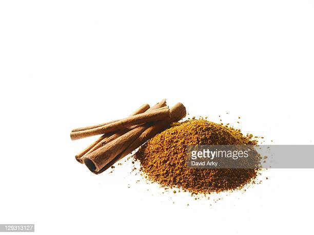 Studio shot of Ground Cinnamon and Cinnamon Sticks on white background
