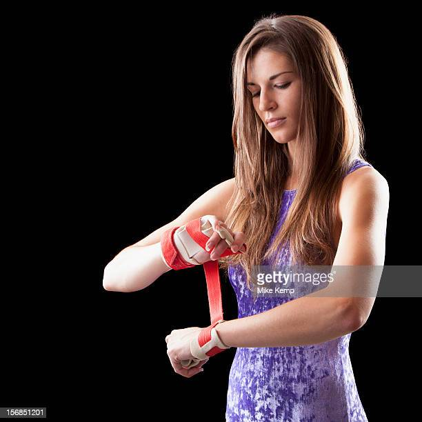 Studio shot of gymnast putting grips onto hands