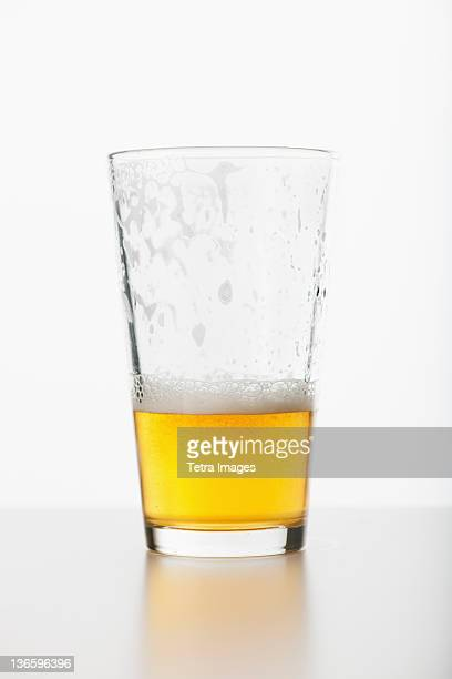 Studio shot of half full beer glass