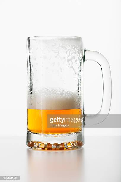 Studio shot of half-full beer glass