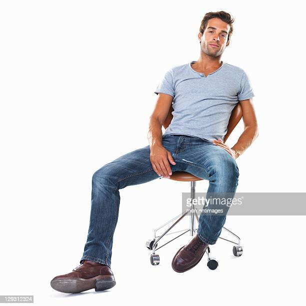 Studio shot of handsome young man sitting comfortably on chair